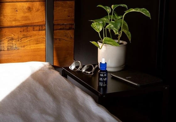 Eir health CBD Isolate 15 on the nightstand next to the bed a book and glasses